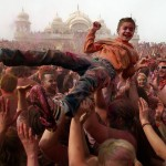 A young boy is hoisted up by the crowd during the Holi Festival of Colors at the Sri Sri Radha Krishna Temple in Spanish Fork, Utah